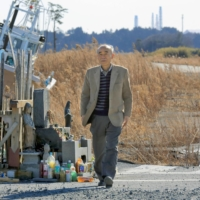 Tetsuro Tsutsui, a member of the Citizens' Commission on Nuclear Energy, walks in Namie, Fukushima Prefecture, to watch the tsunami-hit area in February in 2014. | KYODO