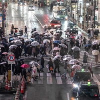 People cross a street in Tokyo's Shibuya Ward on Friday.