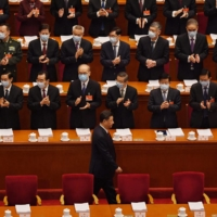 Delegates applaud as Chinese leader Xi Jinping arrives for the opening ceremony of the National People's Congress at the Great Hall of the People in Beijing on Friday. | AFP-JIJI