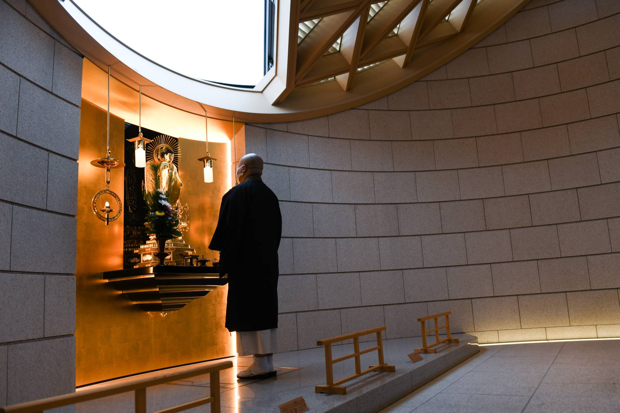 A priest offers a prayer inside a 'common grave' at Tsukiji Hongwanji temple in Tokyo on Feb. 2. | BLOOMBERG