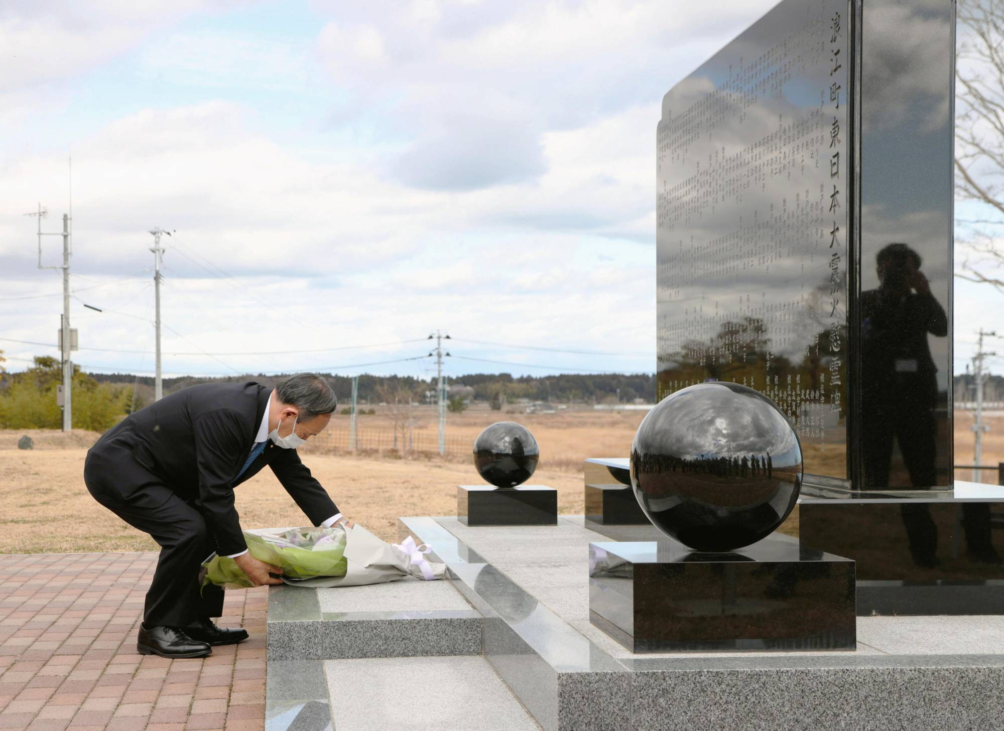 Prime Minister Yoshihide Suga offers flowers at the Great East Japan Earthquake cenotaph in Namie, Fukushima Prefecture, on Saturday. | POOL / VIA KYODO