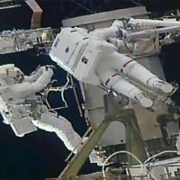 Soichi Noguchi (left) and his colleague are shown on a spacewalk outside the International Space Station on Friday. | NASA / VIA KYODO