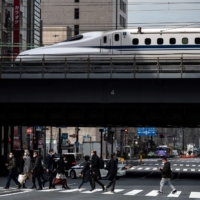People cross a street while a shinkansen arrives in Tokyo on Friday. | AFP-JIJI