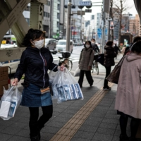 A vendor replenishes her stall with boxes of face masks in Tokyo on Friday. | AFP-JIJI