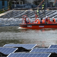 Workers prepare for construction of a floating solar power farm on Tengeh reservoir in Singapore.  | AFP-JIJI
