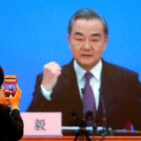 Chinese Foreign Minister Wang Yi is displayed on a screen as he attends via video link a news conference on the sidelines of the National People's Congress in Beijing on Sunday. | REUTERS