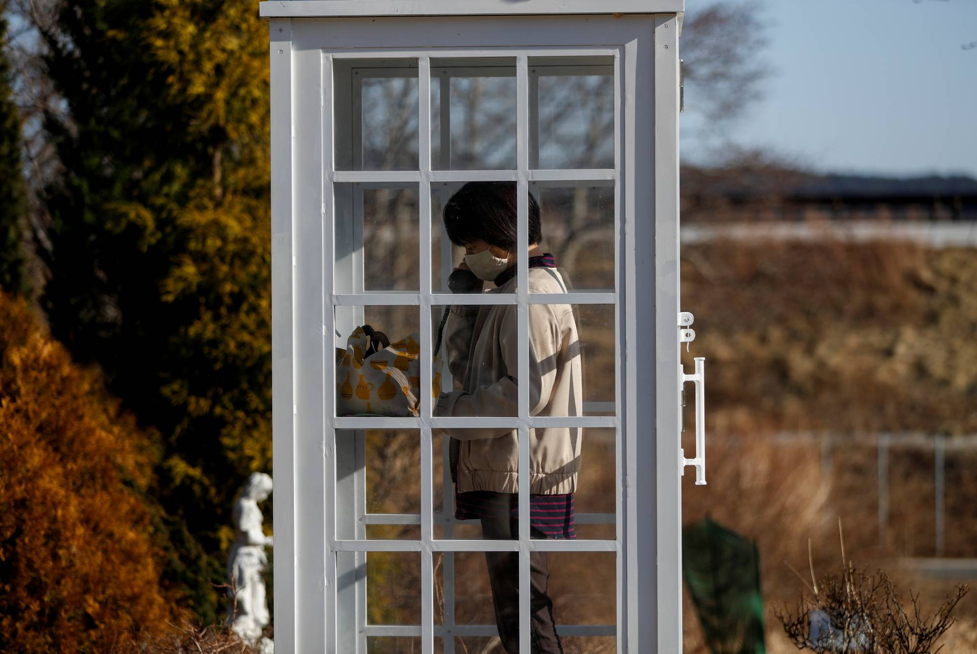 A woman from Ofunato, Iwate Prefecture, who lost her junior high school classmates in the March 11, 2011 earthquake and tsunami, calls her late friends from 'the phone of the wind.' | REUTERS