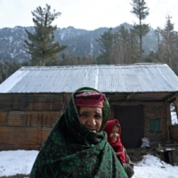 A family from the Gujjar tribe stand near a log house that was partially dismantled by forest officials, about two kilometers from Pahalgam in the Anantnag district of Jammu and Kashmir, India, on Dec. 14, 2020. | AFP-JIJI