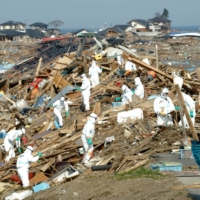Disaster response workers search for missing people in the Ukedo district of the town of Namie, Fukushima Prefecture, on April 14, 2011. That day, they found 10 bodies. | TADAO FURUKAWA / COURTESY OF FUKUSHIMA MINPO