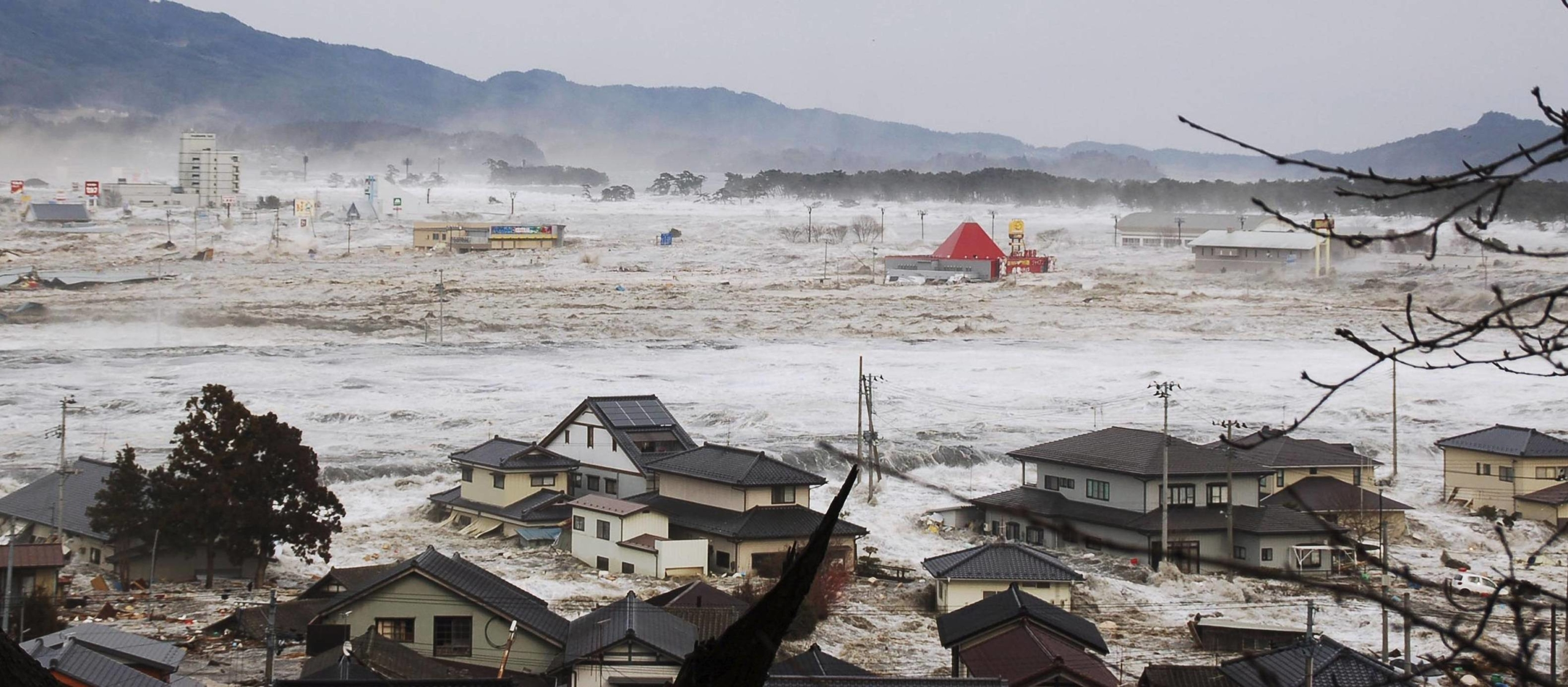 The city of Rikuzentakata, Iwate Prefecture, is flooded after an earthquake-triggered tsunami swept away the area on March 11, 2011, in this supplied photo. The meteorological agency's initial warning was criticized after the disaster for underestimating the size of the tsunami. | KYODO