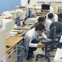 Practice makes perfect: Municipal officials in Osaka hide under their desks during an emergency drill to prepare for a Nankai Trough mega-quake.  | KYODO
