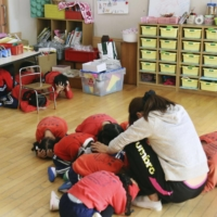 Start early: Kindergarten students take part in an earthquake drill in Amagasaki, Hyogo Prefecture. The area is expected to be hit hard when a Nankai Trough mega-quake occurs.  | KYODO