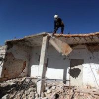 A member of the Syrian Civil Defense (White Helmets) breaks off a roof slab damaged due to bombardment by pro-government forces, in Ibdita village in the Jabal al-Zawiya region of the rebel-held northern countryside of Syria's Idlib province on Feb. 14.   AFP-JIJI