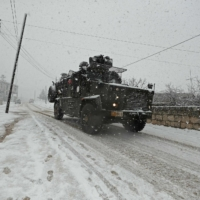 A Turkish military vehicle advances in snowy weather on a road in the Jabal al-Zawiyah area in Syria's southern Idlib province on Feb. 17.   AFP-JIJI