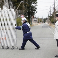 A security guard opens a gate barring entry to parts of Okuma, Fukushima Prefecture, on Monday, as the government eased restrictions on short-term visits to the area. | KYODO