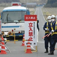 Police officers stand at a checkpoint in Minamisoma, Fukushima Prefecture, on April 11, 2011. The area was made off-limits a month after a meltdown disaster occurred at the Fukushima No. 1 nuclear power plant. | KYODO