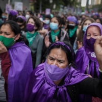 Women demonstrate to demand rights and gender equality during an International Women's Day rally in Bogota on Monday. | BLOOMBERG