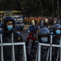 Police and military forces stand by on Feb. 9 in Yangon, Myanmar, as tens of thousands of people gather on University Avenue Road to protest against the military's seizure of power. | THE NEW YORK TIMES
