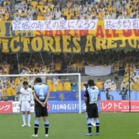 Frontale and Vegalta players hold a moment of silence before their J. League first-division game on April 23, 2011, in Kawasaki. | KYODO
