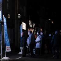 Customers wait in line outside a coronavirus testing site in the Akihabara shopping district of Tokyo on Feb. 24. | BLOOMBERG