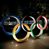 The Olympic rings are illuminated in front of the National Stadium in Tokyo in January.  | REUTERS