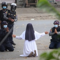 A nun pleads with police not to harm protesters in Myitkyina in Myanmar's Kachin state, on March 9.  | MYITKYINA NEWS JOURNAL / VIA AFP-JIJI