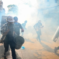 Protesters run after tear gas was fired during a demonstration against the military coup in Yangon, Myanmar, on Tuesday. | AFP-JIJI