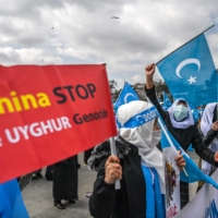 Members of a women's Uyghur group hold signs and flags as they demonstrate near the Chinese consulate in Istanbul on Monday.  | AFP-JIJI