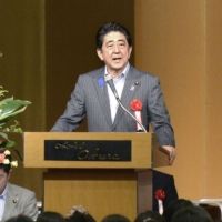 Then-Prime Minister Shinzo Abe addresses a national convention of an organization for private kindergartens' parent-teacher associations held in Tokyo in July 2015. | KYODO