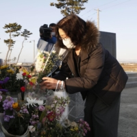 A woman offers flowers at a memorial cenotaph in Sendai on Thursday, the 10th anniversary of the Great East Japan Earthquake. | KYODO