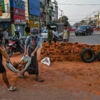 Protesters carry bricks to construct a makeshift barricade during demonstrations in Yangon on Tuesday.  | AFP-JIJI