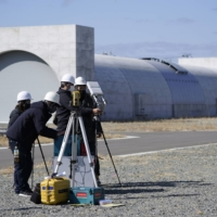 Denso Corp. workers prepare for a drone research next to a mock-up tunnel at Fukushima Robot Test Field. | BLOOMBERG