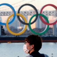 A man walks past the Olympics rings in Tokyo on Jan. 13. | REUTERS