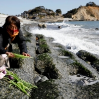 A woman places flowers to mourn the victims of the March 11, 2011, earthquake and tsunami disaster on its 10th anniversary Thursday in the city of Iwaki, Fukushima Prefecture. | REUTERS