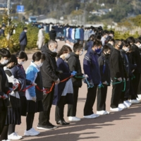 Students in the town of Hirono, Fukushima Prefecture, observe a minute of silence at 2:46 p.m. Thursday, exactly ten years after the magnitude 9.0 earthquake hit northeastern Japan. They held a ribbon to maintain their distance amid the novel coronavirus pandemic. | KYODO