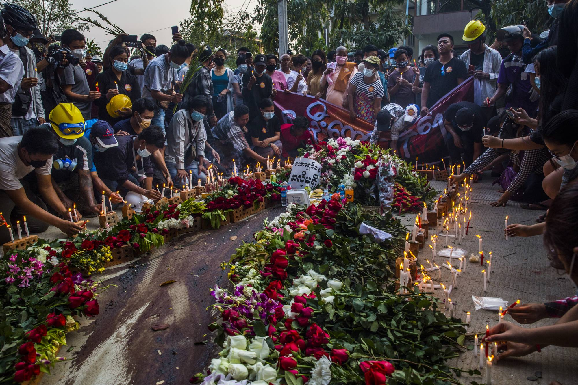 People lay down flowers and light candles at the site where Ko Chit Min Thu, who was shot in the head and killed by security forces while protesting the military coup in North Dagon township in Yangon, Myanmar, on Thursday. | THE NEW YORK TIMES