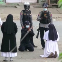 Nun Ann Rose Nu Tawng kneels in front of police officers as she asks security forces to refrain from violence against children and residents amid protests in Myitkyina, Myanmar, on March 9. | MYITKYINA NEWS JOURNAL / VIA REUTERS