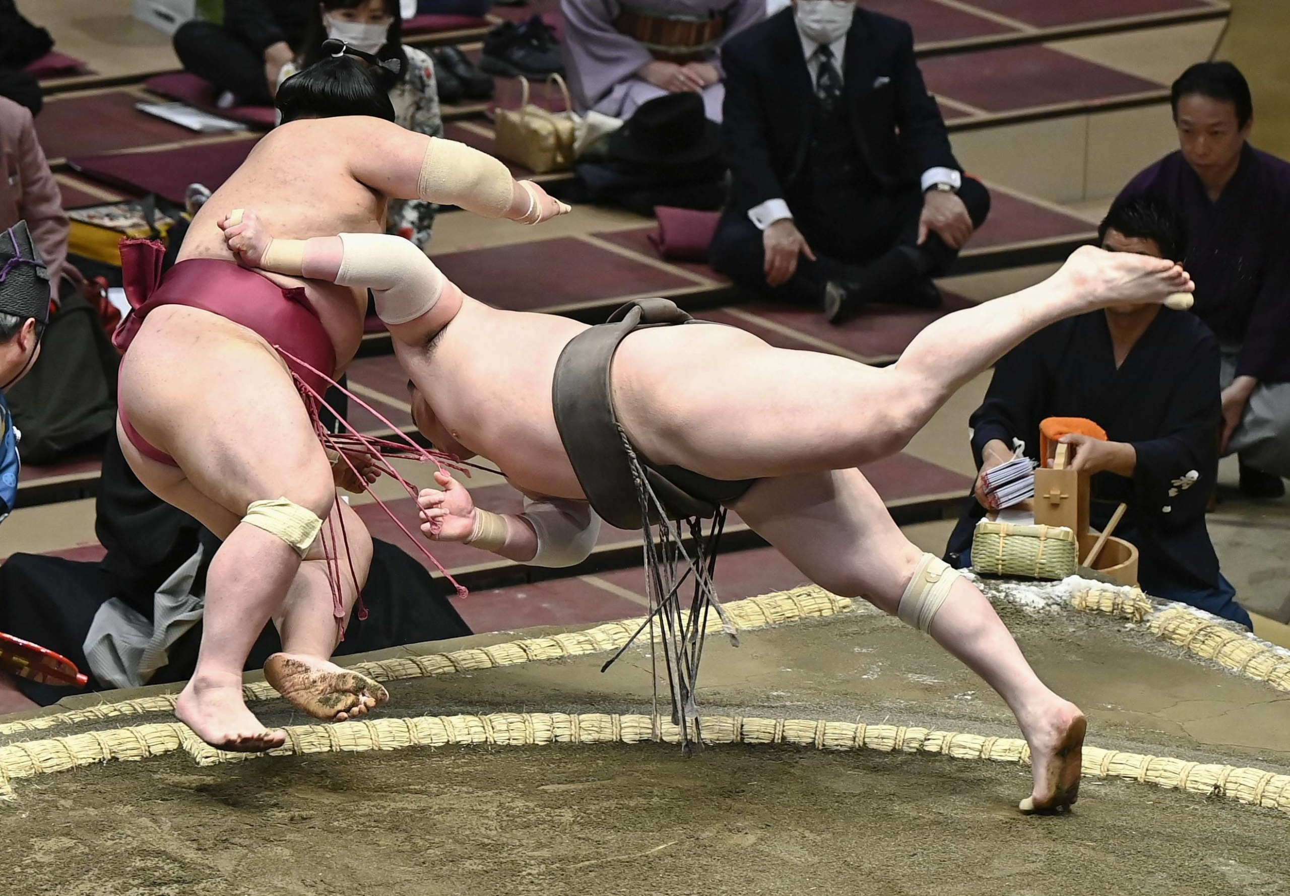 Hakuho (right) forces out Daieisho in their Day 1 bout during the Spring Grand Sumo Tournament on Sunday at Ryogoku Kokugikan. | KYODO