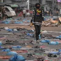 A protester walks in a street full of water bags to be used against tear gas, during an anti-coup protest at Hledan junction in Yangon, Myanmar, on Sunday. | REUTERS
