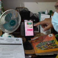 Teacher Kristhean Navales conducts an online class using his mobile phone at his home in Quezon City, suburban Manila. | AFP-JIJI