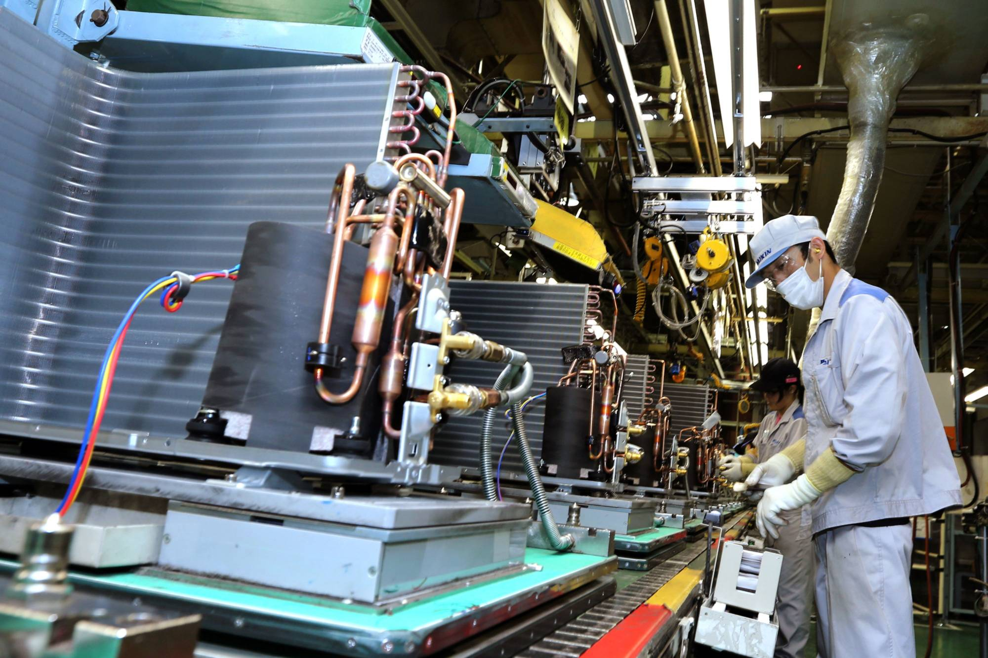 Workers assemble outdoor air conditioner units on the production line of Daikin Industries Ltd.'s plant in Kusatsu, Shiga Prefecture, in August 2017. | BLOOMBERG