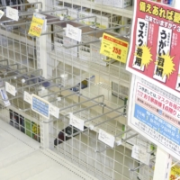 Shelves for face masks are empty at store in Saga amid the pandemic in April last year. | KYODO