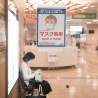 A sign urging people to wear masks is displayed at the Shinjuku Expressway Bus Terminal in Tokyo. Travel agency H.I.S. saw its sales plunge 80% as inbound tourism plummeted amid the coronavirus pandemic. | BLOOMBERG