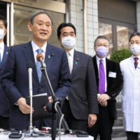 Prime Minister Yoshihide Suga speaks to reporters after getting his first dose of a COVID-19 vaccine at at the National Center for Global Health and Medicine in Tokyo on Tuesday. | POOL / VIA KYODO