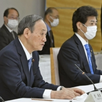 Prime Minister Yoshihide Suga speaks at a meeting of Cabinet ministers on Tuesday regarding emergency financial support measures for people suffering from the economic hardships amid the coronavirus pandemic. | KYODO