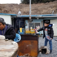 Kim Si-young, 66, cooks oysters for siblings Lyoo Chan-hee, 10, and Lyoo Chae-hee, 7. | REUTERS
