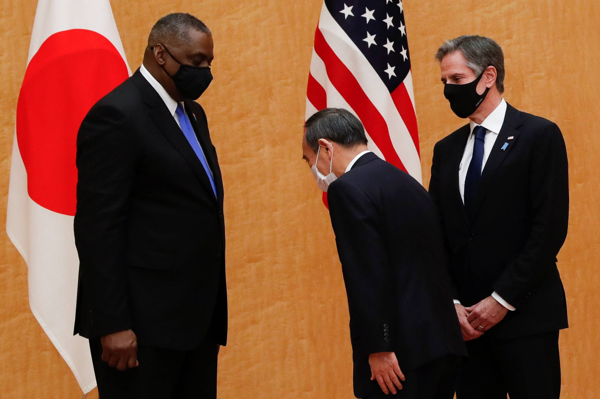 U.S. Secretary of State Antony Blinken and Defense Secretary Lloyd Austin meet with Prime Minister Yoshihide Suga (center) at his office in Tokyo on Tuesday. | POOL / VIA REUTERS