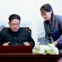 North Korean leader Kim Jong Un signs a guest book as his sister, Kim Yo Jong, looks on during an inter-Korean summit at the Peace House building on South Korea's side of the truce village of Panmunjom in April 2018. | KOREA SUMMIT PRESS POOL / VIA AFP-JIJI