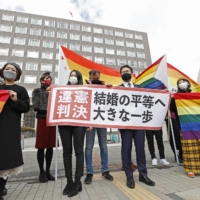 Lawyers and supporters of plaintiffs hold signs and flags outside the Sapporo District Court on Wednesday hailing a court decision that said Japan's failure to recognize same-sex marriage is unconstitutional. The sign says that the ruling is a 'big step forward for marriage equality.'  | KYODO