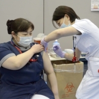 A medical worker receives a COVID-19 vaccine shot at a hospital in Toyoake, Aichi Prefecture, earlier this month. | KYODO